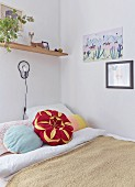Flower-shaped cushion on bed below wall lamp and shelf in corner