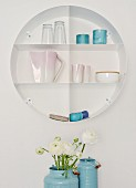 Circular shelving holding china and glasses; white ranunculus in blue enamel churns