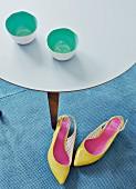 Trinkschalen - innen mintgrün - auf filigranem Beistelltisch und knallgelbe Pumps auf dem Teppich