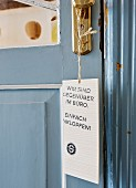 Sign hanging from brass door handle on interior door