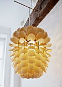 Hand-crafted lampshade made from delicate wooden scales hung from wooden rod