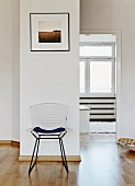Classic mesh chair against wall with view into adjoining room through open door