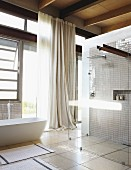 Light-flooded bathroom with walk-in designer shower and free-standing bathtub against steel and glass facade