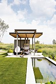 Pond and steel girder gazebo in landscaped garden surrounded by wild countryside