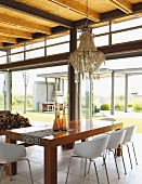 Chandelier above dining set with elegant wooden table and shell chairs; view into garden through steel and glass facade