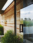 Facade of modern house with rammed-earth structure and reflection of surrounding countryside in glass door