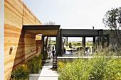 Modernes Haus mit Stahlglasfassade und Lehm-Wandflächen mit dekorativer Querstruktur