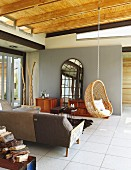 Designer sofa, wicker hanging chair and lattice cheval mirror in open-plan interior with tiled floor