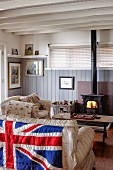 Sofa with Union Flag hung over backrest opposite fire in log burner in rustic interior with wood panelling and wood-beamed ceiling