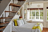 Double bed next to built-in bathtub below window in wood-panelled bedroom with staircase in foreground