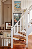 Wooden staircase with white balustrade in open-plan stairwell of beach house