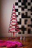 Modern Christmas tree made from metal frame with pink silk ribbon