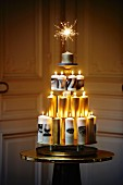 Modern Christmas tree made from pyramid of white and gold candles with sparkler at the top