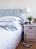 Bed with upholstered headboard and white bed linen next to bedside cabinet with table lamp and white lampshade; slippers on sisal carpet