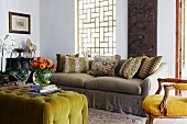Ottoman with lime green cover and colourful bouquet in vase opposite sofa below window with wooden lattice framework; antique, upholstered armchair to one side
