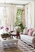 Couchtisch mit weißem Lederbezug und Rattan Sofa auf Teppich mit geometrischem Muster, geraffter Vorhang an Metallgitter Türelementen