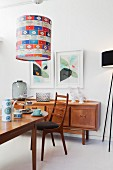 Chair at set table below pendant lamp with colourful lampshade; sideboard below framed pictures on wall in background