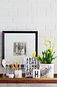 Still-life arrangement of potted narcissus, beakers, various glass vessels and framed picture on whitewashed brick wall