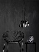 Wire mesh chair and matte grey vase on side table below bundle of shiny, metallic lampshades against black wall