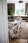 View through open door of armchairs with pattern of stylised leaves on upholstery in interior with rustic ambiance
