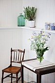 Glass vase of wildflowers on console table next to antique wooden chair