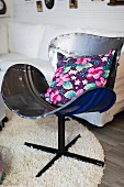 Floral cushion on vintage chair made from recycled metal and long-pile rug