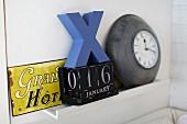 Vintage arrangement of old enamel sign, perpetual calender and clock on shelf
