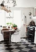 Rustikale Küche mit Schachbrettmusterboden, Stühle mit weissen Hussen am Esstisch vor Fenster, seitlich Vintage Küchenofen