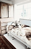 Animal-skin rugs on antique bench below window and antique wooden dresser