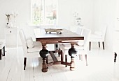 Dark, solid wood table with turned legs and elegant, white upholstered chairs on rustic wooden floor