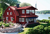 Old, Swedish wooden house with Falu-red facade in park-like gardens by the sea