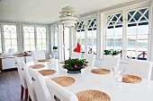 Conservatory ambiance in Swedish country house with classic, Scandinavian lamp above oval dining table with round, raffia place mats