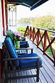 Dark garden furniture with blue cushions on wooden veranda adjoining Swedish wooden house
