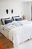 Double bed with Scandinavian-style, blue and white covers below wooden ducks on wall