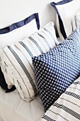 Double bed with blue and white pillows in different patterns