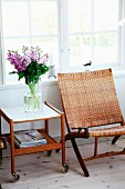 Bouquet of stocks on 50s serving trolley and retro, classic easy chair with woven paper cord seat and backrest