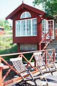 Deckchairs on wooden jetty with red railing in front of Swedish wooden house by the sea