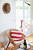 Seating area with wicker furniture next to open French windows with sea view