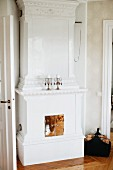 Antique, white fireplace with copper door and two candlesticks on mantelpiece in traditional interior