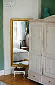 Pale farmhouse cupboard next to gilt-framed mirror on wall and small foot stool