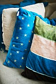 Stack of scatter cushions with patterns of stripes and stars