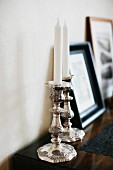 White candles in silver candlesticks on top of chest of drawers