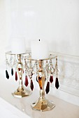 Candlesticks with colourful glass pendants and white pillar candles on mantelpiece