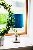 Table lamp with blue fabric lampshade next to potted ivy topiary on windowsill