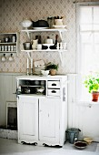 Half-height cabinet painted white below crockery on bracket shelves in rustic kitchen