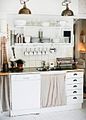 Functional kitchen counter with integrated dishwasher and drawers below cups and crockery on white, wall-mounted shelves