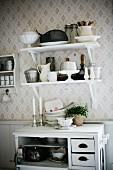 Crockery on bracket shelves on patterned wallpaper above white-painted half-height cabinet