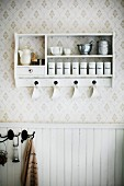 Storage jars and kitchen utensils on white spice rack on wallpapered wall