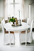 Chairs with white, loose covers around house plant on tray on table in rustic dining room
