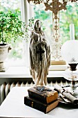 Madonna figurine and antiquarian books next to paraffin lamp in front of window